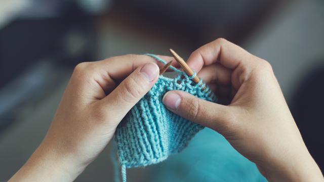 hands knitting blue yarn