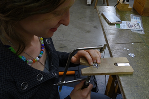 Student metalsmithing in a jewelry-making class